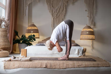 Attractive senior woman working out standing in Uttanasana at home.