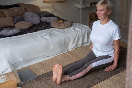 Senior woman practicing yoga, sitting in Dandasana exercise, Staff pose, working out