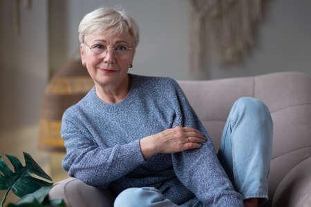 Senior caucasian woman relaxing at home sitting on sofa. Zdjęcie Seryjne - 157897454