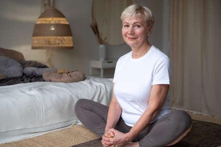 Senior caucasian woman doing yoga or pilates training, sitting in Purna Titli, Baddha Konasana Zdjęcie Seryjne