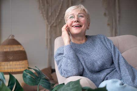 Senior woman smiling talking on phone at home