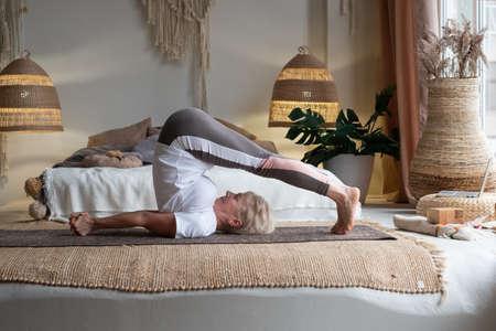 Sporty senior woman doing halasana, plough pose or yin yoga snail posture Zdjęcie Seryjne