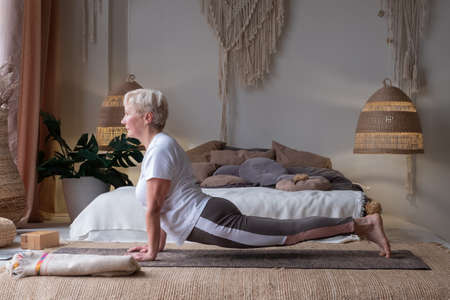 senior caucasian woman working out, doing urdhva mukha shvanasana or upward facing dog pose Zdjęcie Seryjne - 157932224