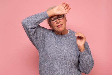 Senior tired woman touching forehead for illness and fev