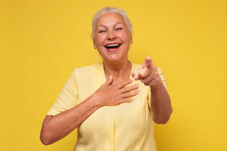 Middle age senior woman laughing at you, pointing finger to the camera. It is a great joke
