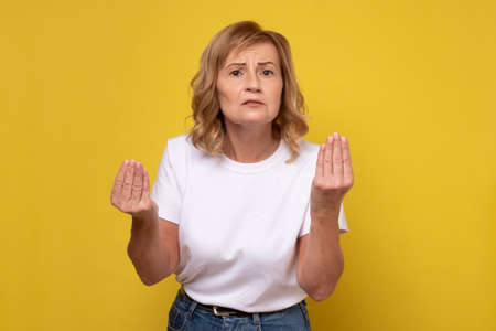 Mature woman doing Italian gesture with hand and fingers trying to explain her point of view. Фото со стока
