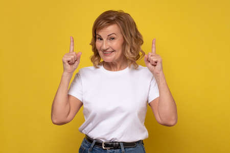 Senior smiling woman pointing up giving advice.