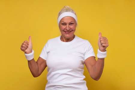 Active elderly woman holding her thumb up