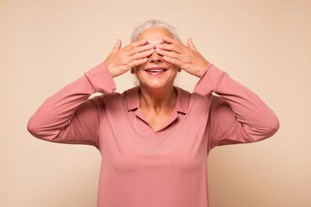 woman closing her eyes with hands going to see surprise prepared by her family waiting for a gift.