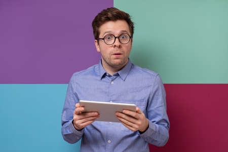 Mature european man using a digital tablet. He is puzzled and confused. Zdjęcie Seryjne