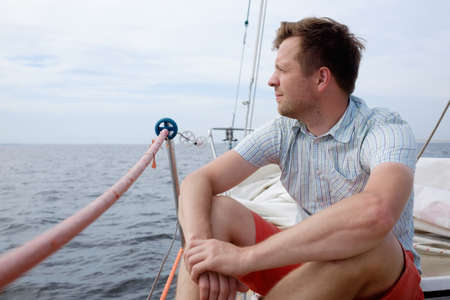 Man sitting on boat sailing on ocean being happy and carefree Zdjęcie Seryjne
