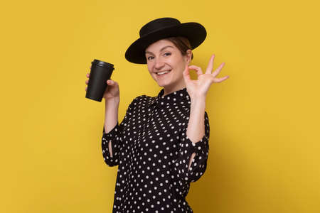 Caucasian woman in black hat holding coffee cup showing ok gesture