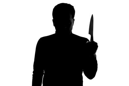 Silhouette of dangerous man with a knife in his hand being aggressive