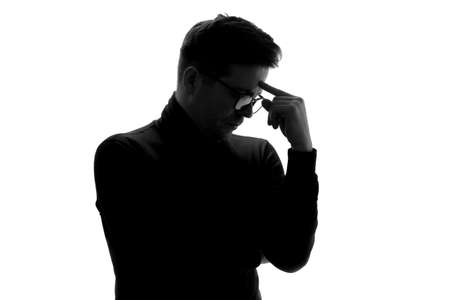 Silhouette of businessman considers his options, thinking about important project.