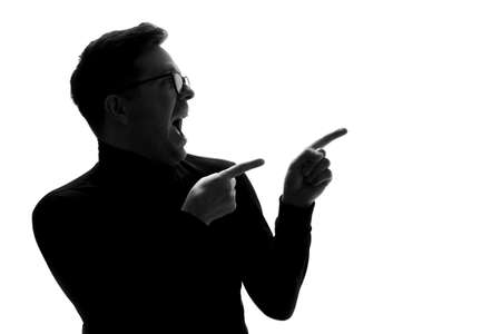 Silhouette of young man pointing aside. Pay attention to this information.
