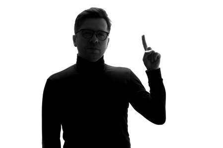 Silhouette of young man showing index finger up, giving advice or recommendation Stockfoto