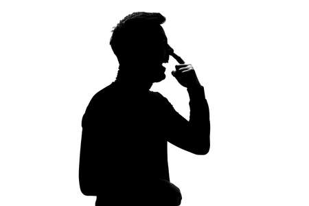 Silhouette of young man drilling his nose with funny face. Bad habbit. Stockfoto
