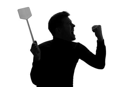 Silhouette of furious man trying to kill mosquito with fly swatter.