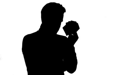 Silhouette of man holding up a few playing cards.