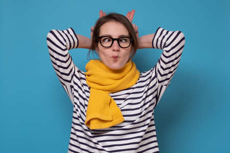 Young caucasian woman in glasses making fish face