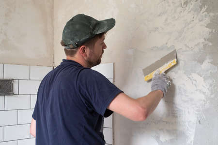 Caucasian man put plaster patching up the cracks on the wall. Zdjęcie Seryjne