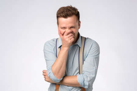 Young caucasian man laughing on funny joke.