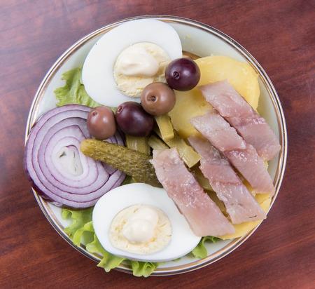 mix salad of fish, potato, egg, and onion on a plate Stock Photo