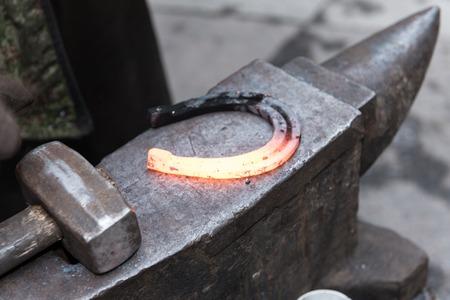 대장장이 도구로 말굽을 만든다.