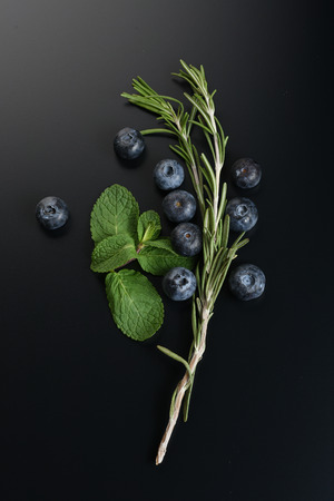 still life of fresh fruits and herbs on a dark background close up