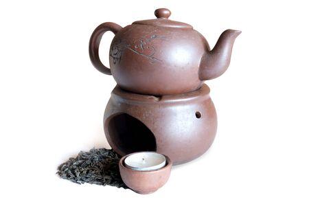 black tea and clay teapot on white background