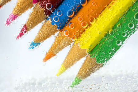 backgraound: pencils into water bubbles, close-up