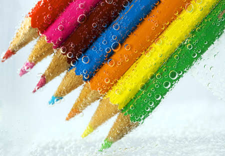 backgraound: colorful pencils, close-up on white background into water bubbles