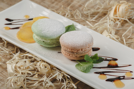 Colorful macaroons in a gift box and marshmallow in coffee cup on wooden table. Sweet macarons and flowers. Top view Stock Photo