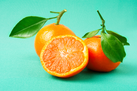 c vitamin: two fresh tangerine on a green background. Stock Photo