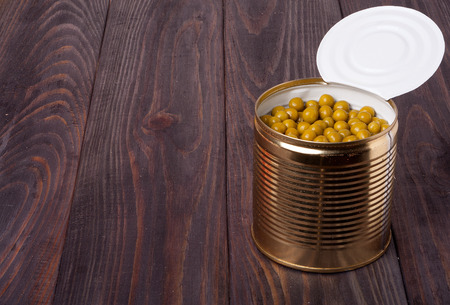 airtight: canned green peas in a bank on wooden table.