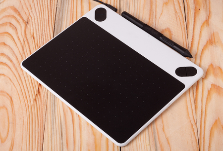 wacom: graphics tablet on wooden background.
