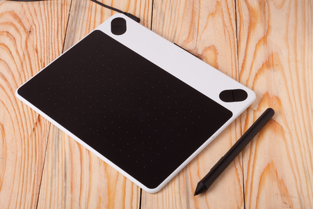 graphics tablet on wooden background.