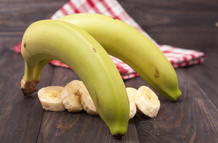 upper half: green banana with slices on wooden background. Stock Photo