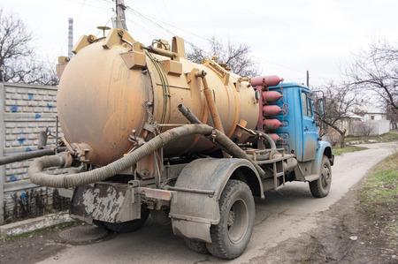 オレンジのタンクで廃棄物収集車。