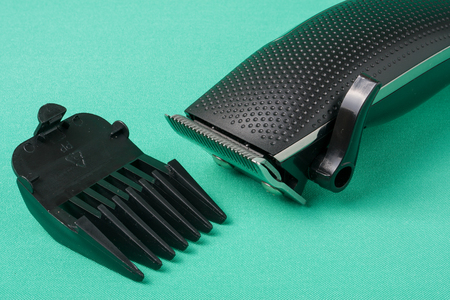 clippers comb: black hair clipper placed on green background.
