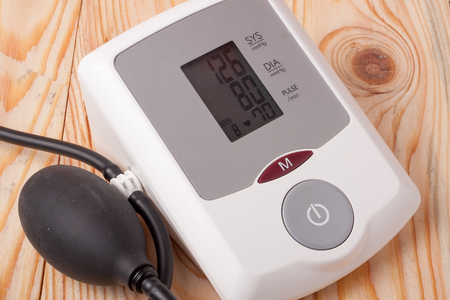 systolic: automatic blood pressure monitor on a wooden background. Stock Photo