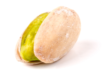 salted: one pistachio isolated on white background close-up macro.