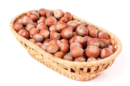 full willow: hazelnuts in a wicker basket isolated on white background. Stock Photo