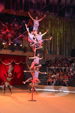 balancing act: LUGANSK ,UKRAINE - APRIL 9, 2016: several acrobats in a circus performance on the pole. Editorial