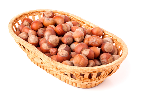 willow fruit basket: hazelnuts in a wicker basket isolated on white background. Stock Photo