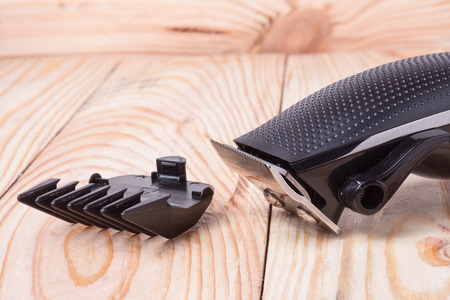 hairclipper: hair trimmer  with attachment on a light wooden background closeup.