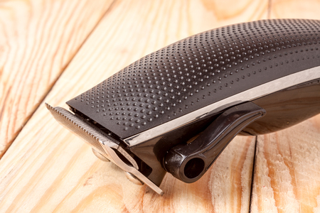 hairclipper: hair trimmer on a light wooden background closeup.