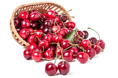 cherries in a wicker basket isolated on white background.