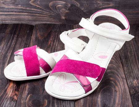 velcro: childs sandals on a dark wooden background.