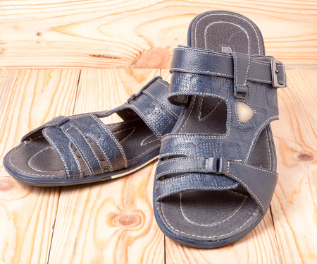 informal clothes: Mens summer sandals on a light wooden background.